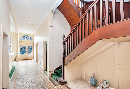 A stunning staircase leads to the upstairs rooms and kitchen.