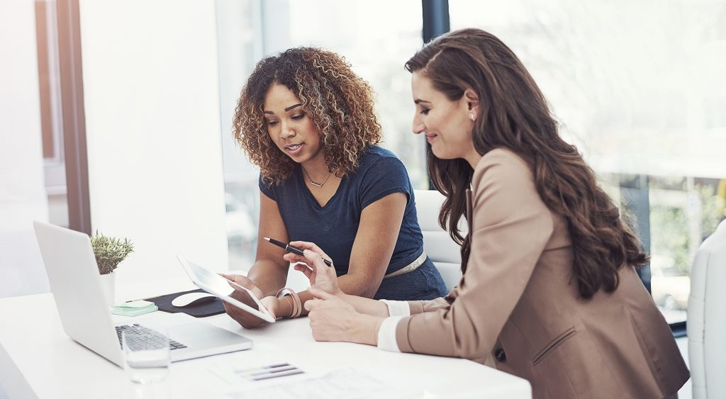 Two women comparing commercial property values