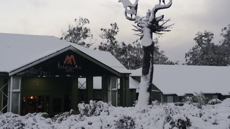 Snow blankets the ground and buildings at Cradle Mountain Hotel